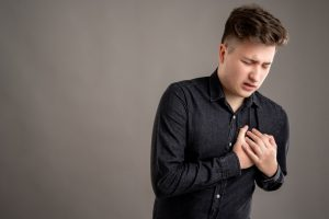 Portrait of serious stylish attractive man dressed with a casual black shirt has cardiac problem