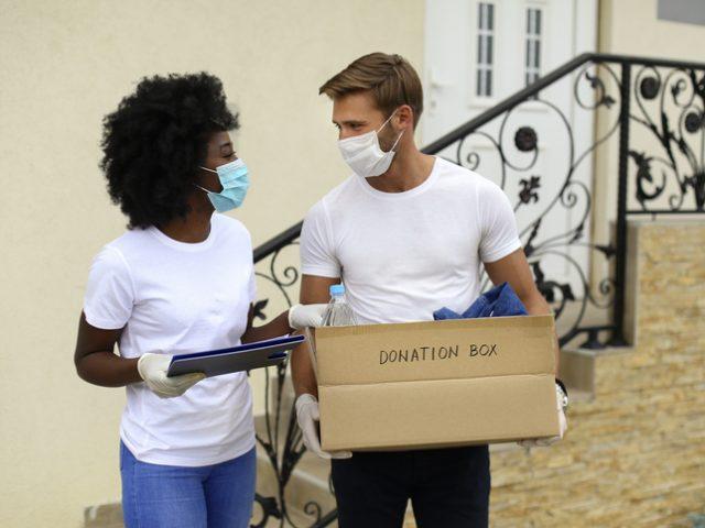Couple iwth mask holding donation box