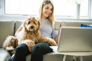Woman sitting on couch with dog