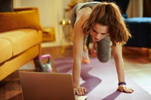 Woman exercising with laptop