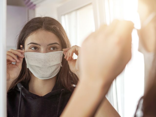 Young woman trying on a face mask