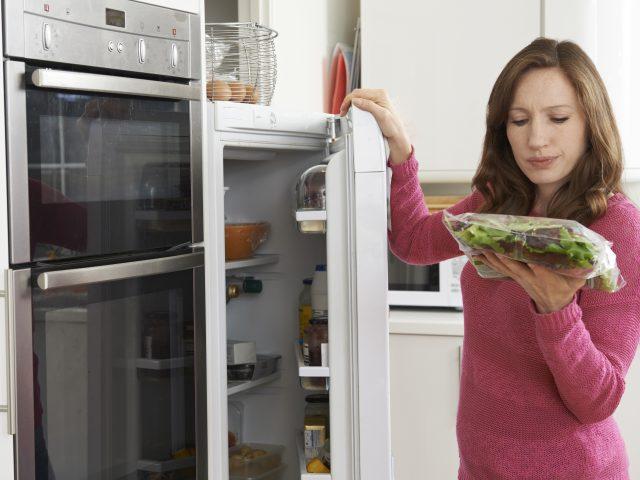 Woman pulling greens from fridge