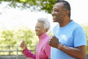 Older couple jogging while smiling