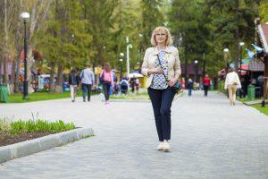 Woman walking down foot path in town