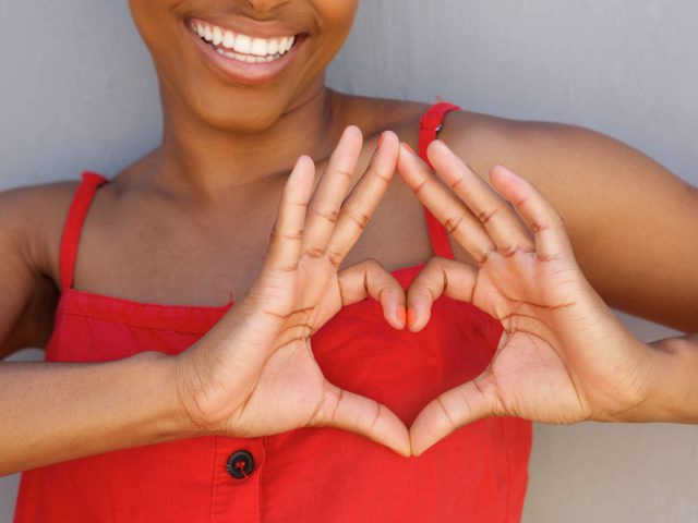 Woman in red dress making heart symbol with her hands.