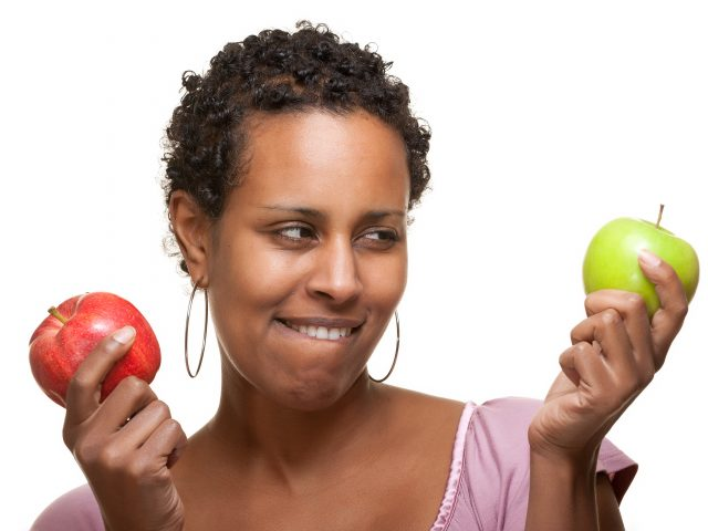 Woman holding two different apples