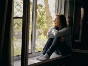 Woman sitting in window sill contemplating