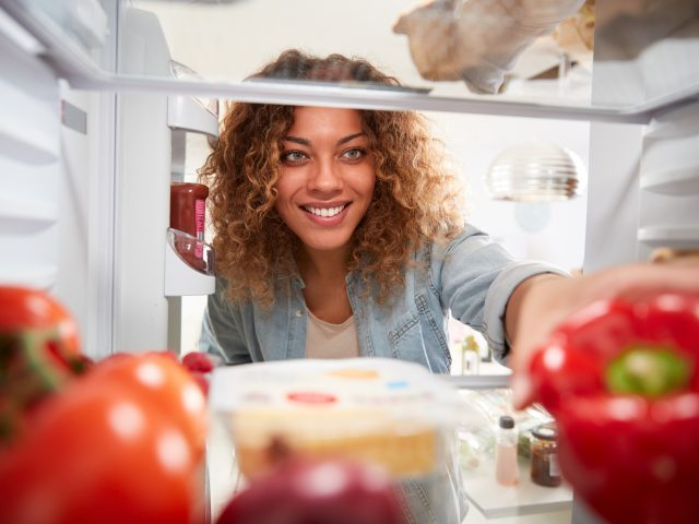 Woman reaching into fridge to grab bell pepper
