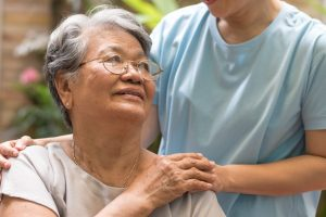 Older woman being comforted with a hand on her shoulder