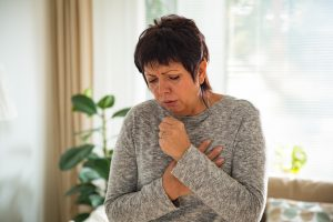 Woman holing her heart while she coughs