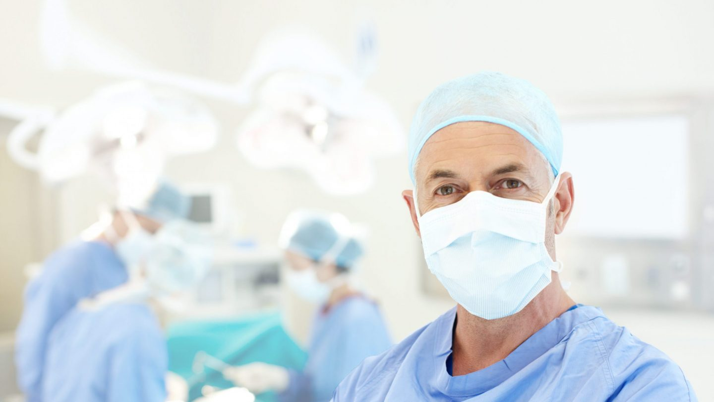 senior surgeon wearing a face mask and hospital scrubs in an operating theatre