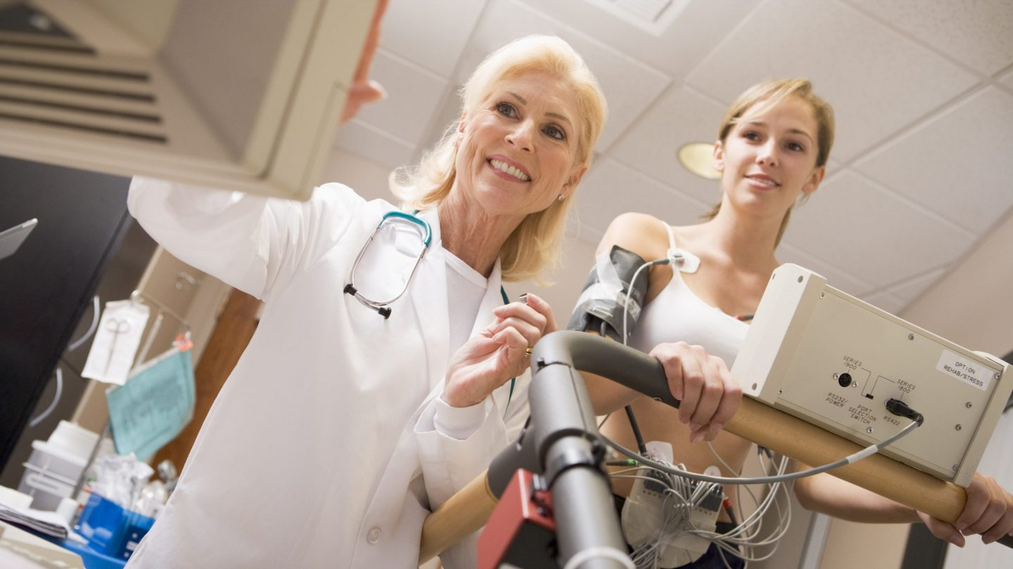 Doctor monitoring patient's vitals on a treadmill stock