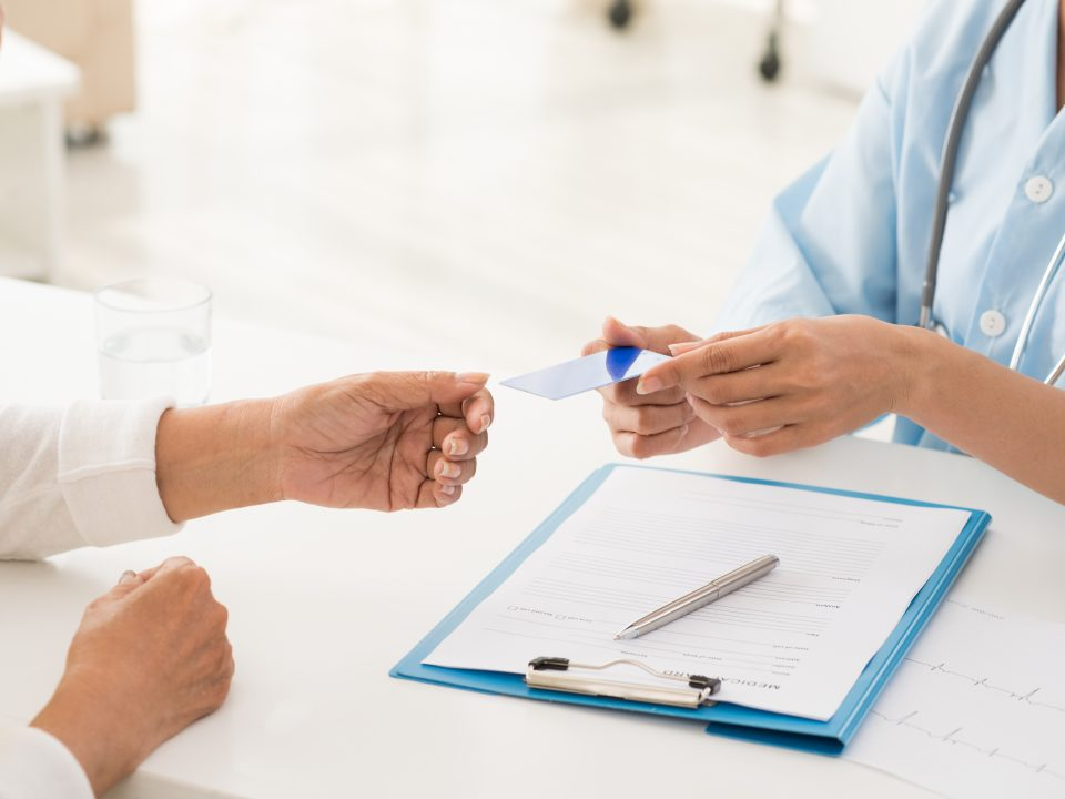 Doctor and patient having a conversation Health insurance card
