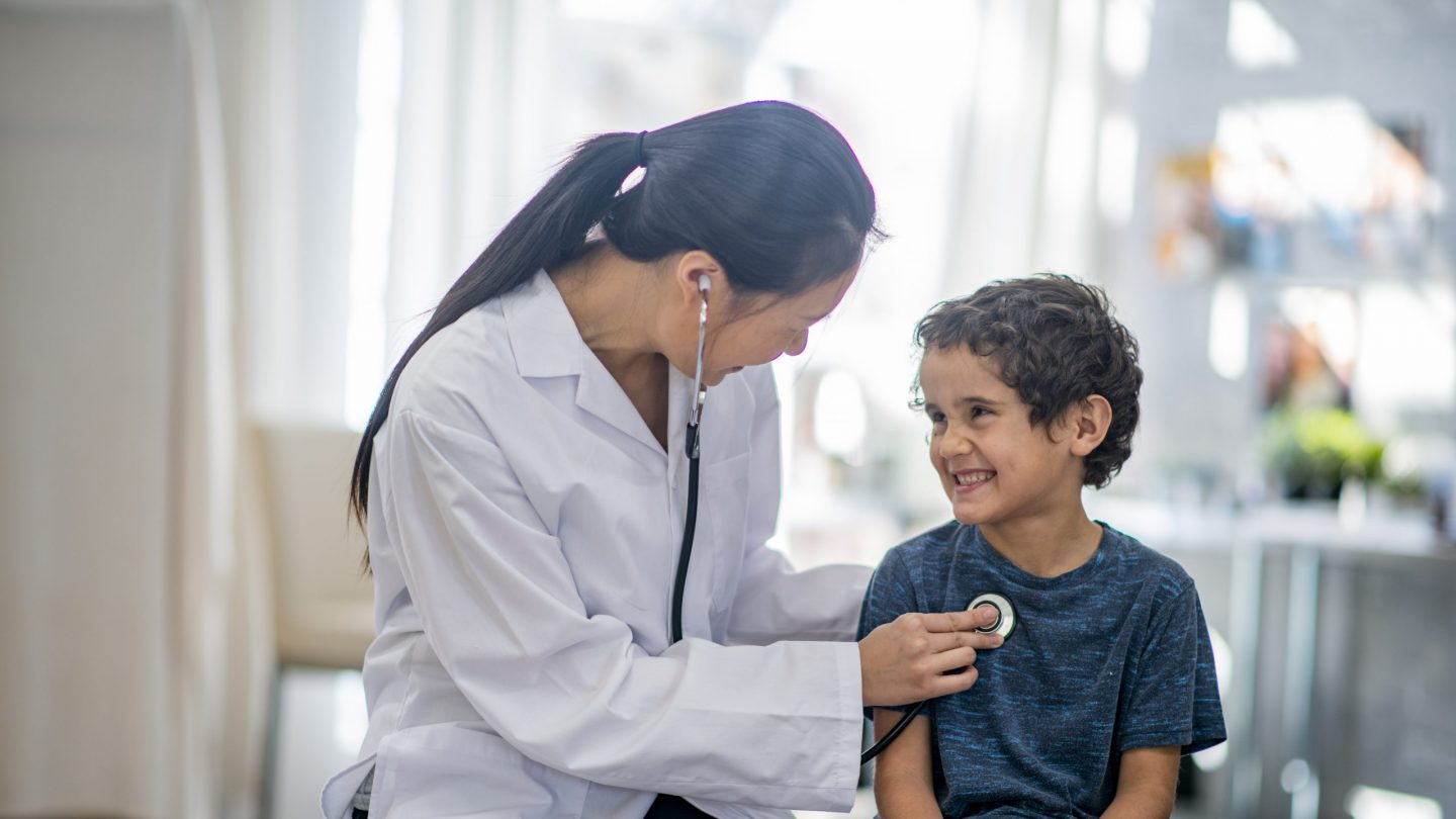 Boy smiling while the doctor checks his heart rate with a stethoscope.