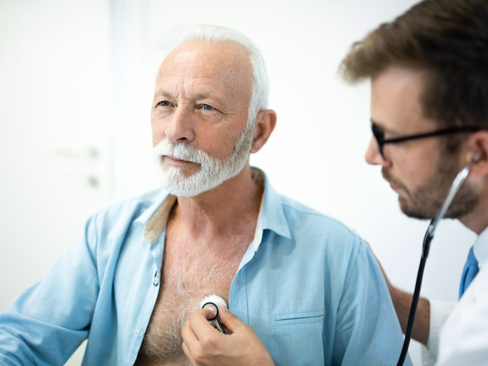 Senior man having his heart examined with stethoscope in hospital.