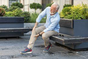 Mature man grabbing leg