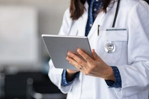 Closeup of female doctor in labcoat and stethoscope holding digital tablet, reading patient report.