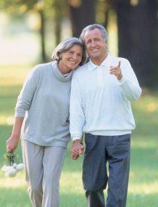 Older couple walking together in a park