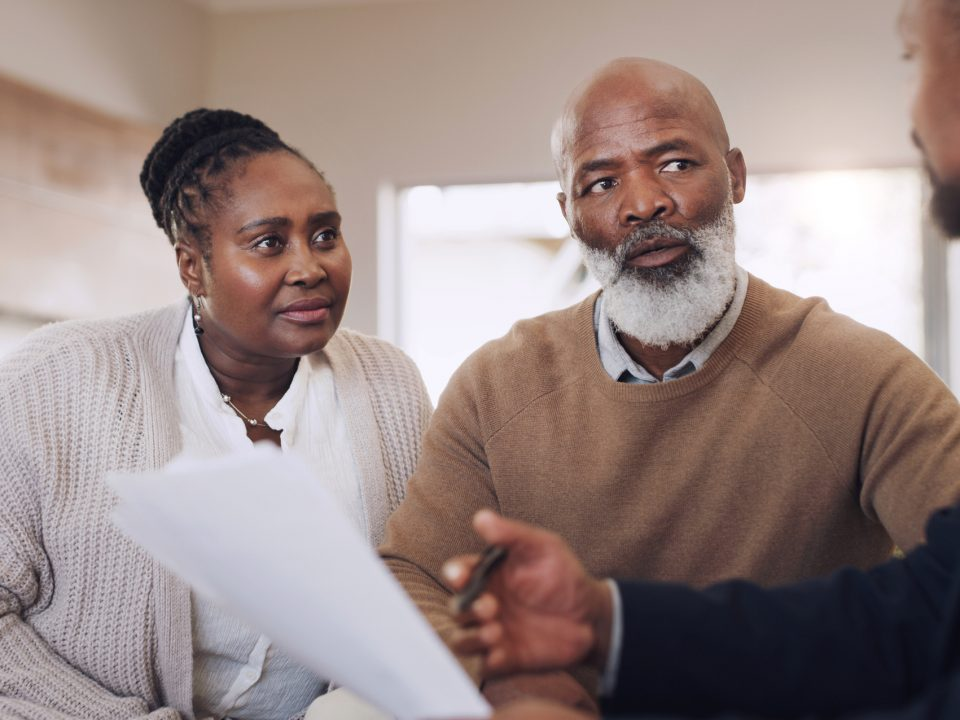 Cropped shot of a senior couple sitting with their financial advisor in their home during the day
